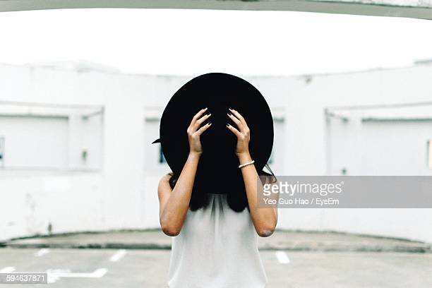 Woman Standing On Street And Covering Face With Hat
