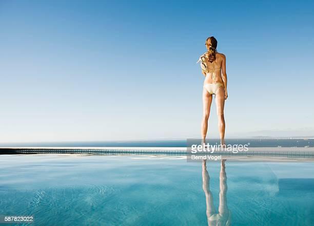 Woman standing on swimming pool ledge