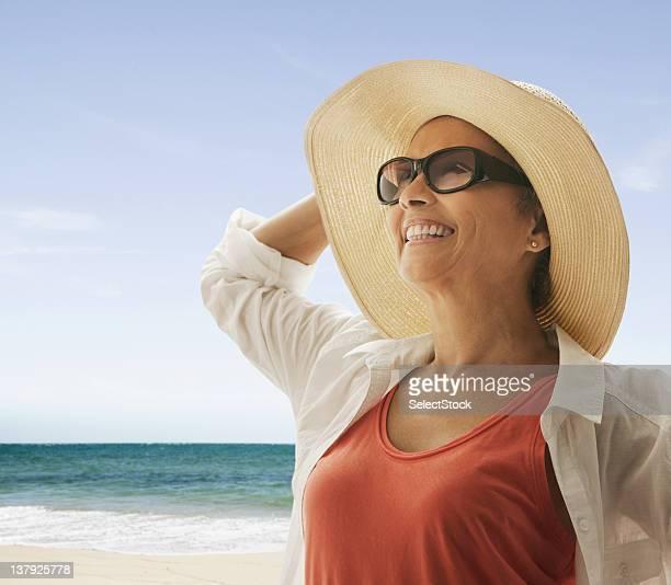 Frau stehen am Strand halten Hut gegen den wind