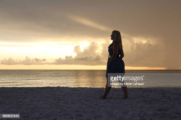 Woman standing on the beach pauses by the seashore
