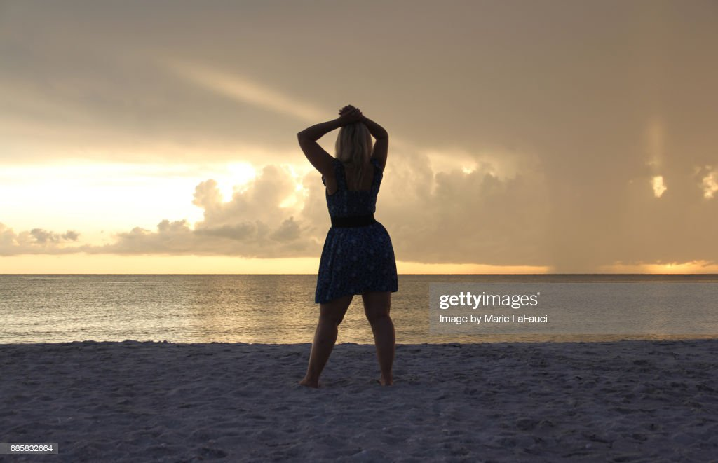 Woman standing on the beach pauses by the seashore : Stock Photo