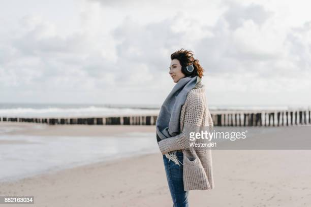 Woman standing on the beach with headphones