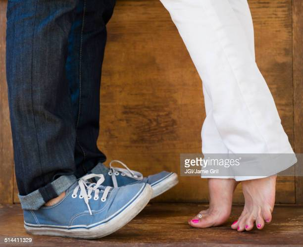 Woman standing on tiptoes to kiss boyfriend