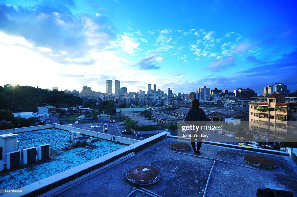 Woman standing on top of building : Stock Photo