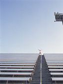 Woman standing on top row of stadium bleachers, reaching arms out