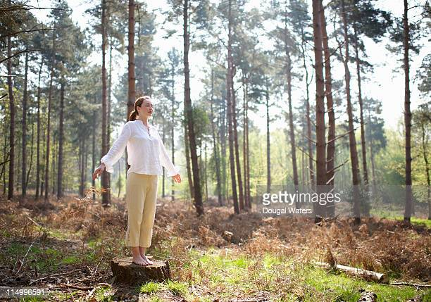 Woman standing on tree stump in woodland.