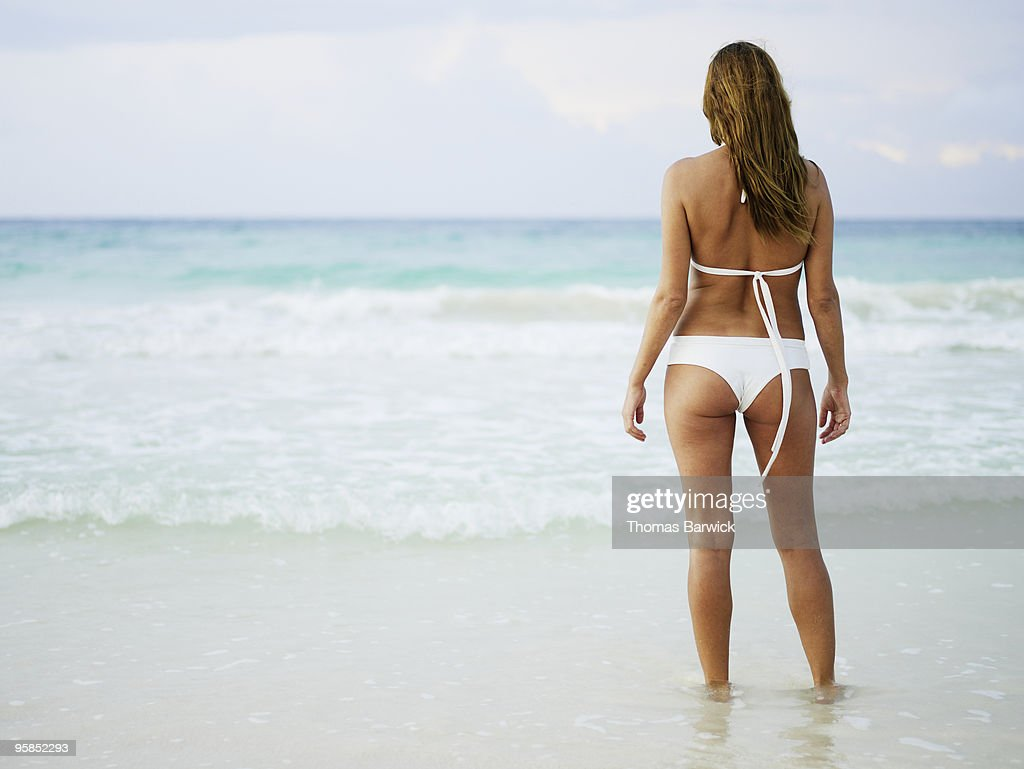 Woman standing on tropical beach looking out : Stock Photo