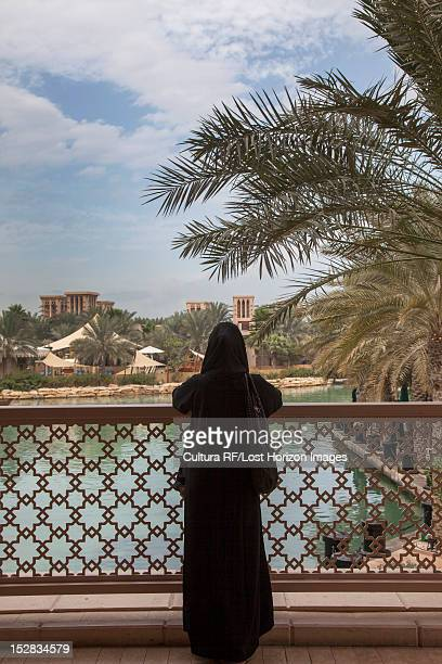 Woman standing on urban bridge