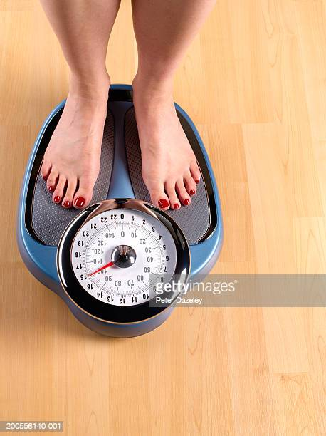 Woman standing on weighing scales on wooden floor, low section