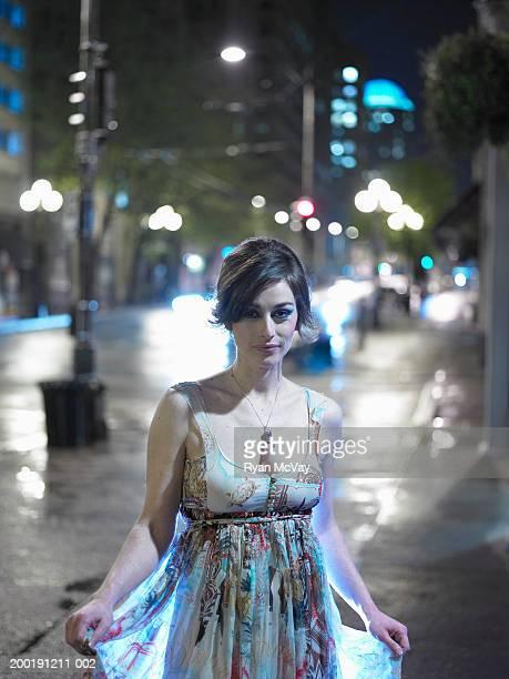 Woman standing on wet sidewalk, night, portrait