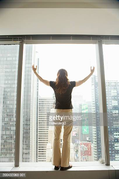 Woman standing on windowsill, arms outstretched, rear view