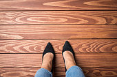 Woman standing on wooden floor. Top view