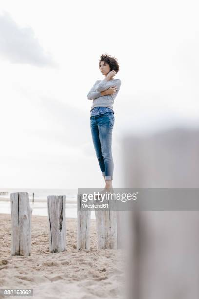 Woman standing on wooden stake on the beach