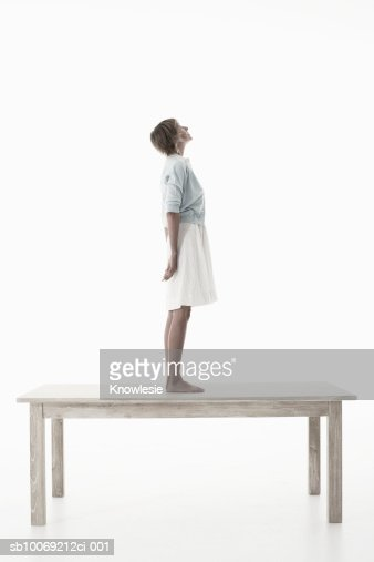 Woman standing on wooden table against white background, side view : ストックフォト