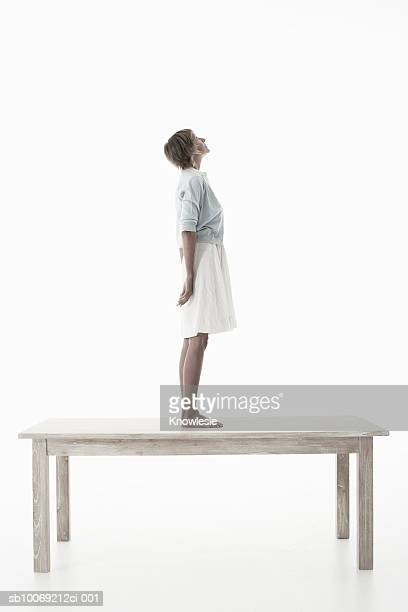 Woman standing on wooden table against white background, side view