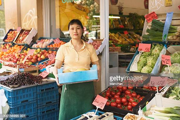 Woman standing outside greengrocers, holding box of melons, portrait