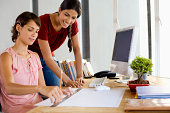 Woman standing over desk of woman drawing with ruler