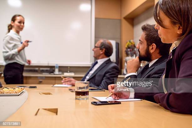 woman standing presenting to sitting businessmen