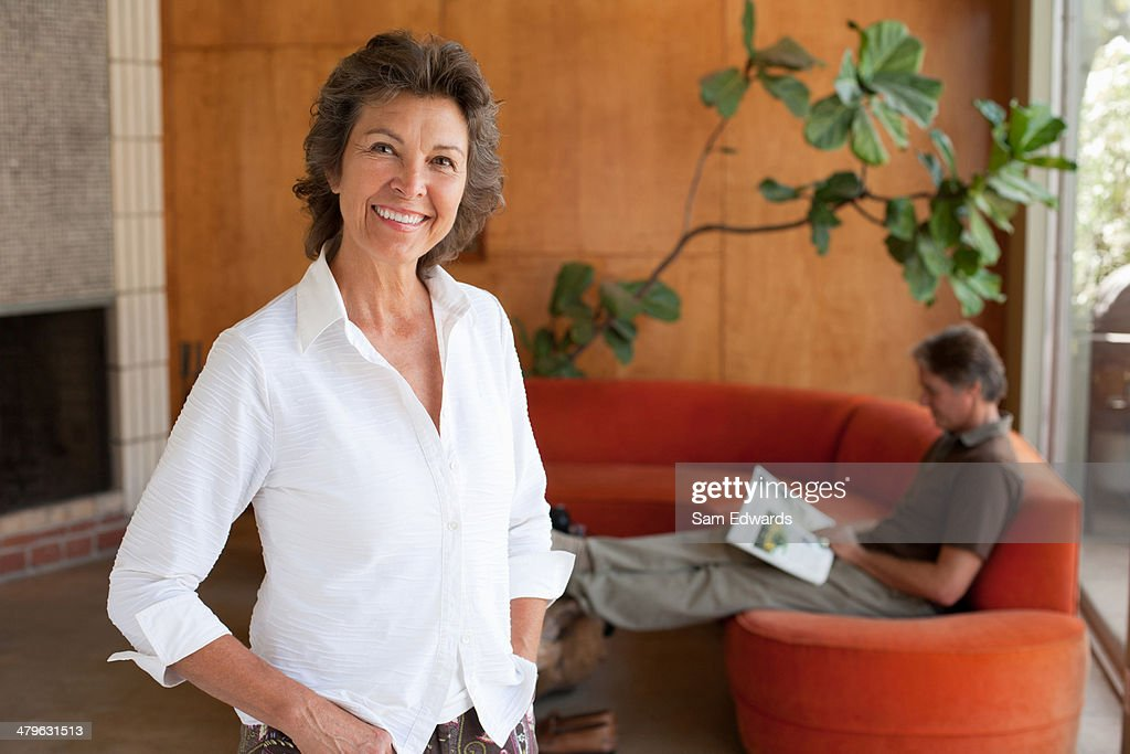 Woman standing smiling in modern home : Stock Photo