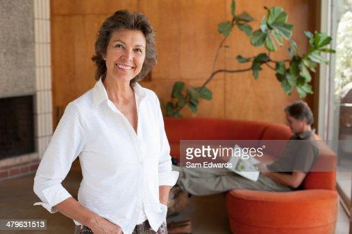 Mulher sorridente em casa moderna de Pé : Foto de stock