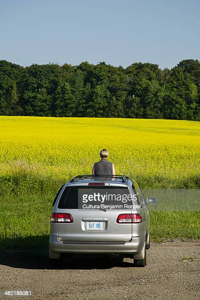 Woman standing through sunroof of car by a field