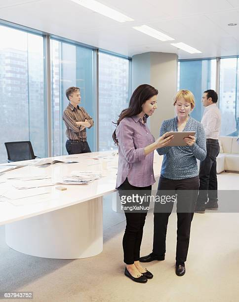 Woman standing together to discuss plans on tablet computer