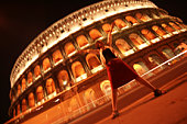 Woman standing triumphantly outside of coliseum in Rome
