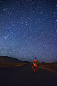 Woman standing under a starry sky.