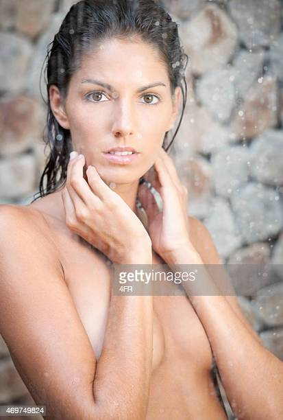 Donna in piedi sotto una doccia a pioggia tropicale in una Spa