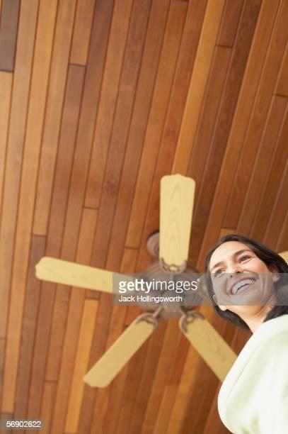 Woman standing under ceiling fan
