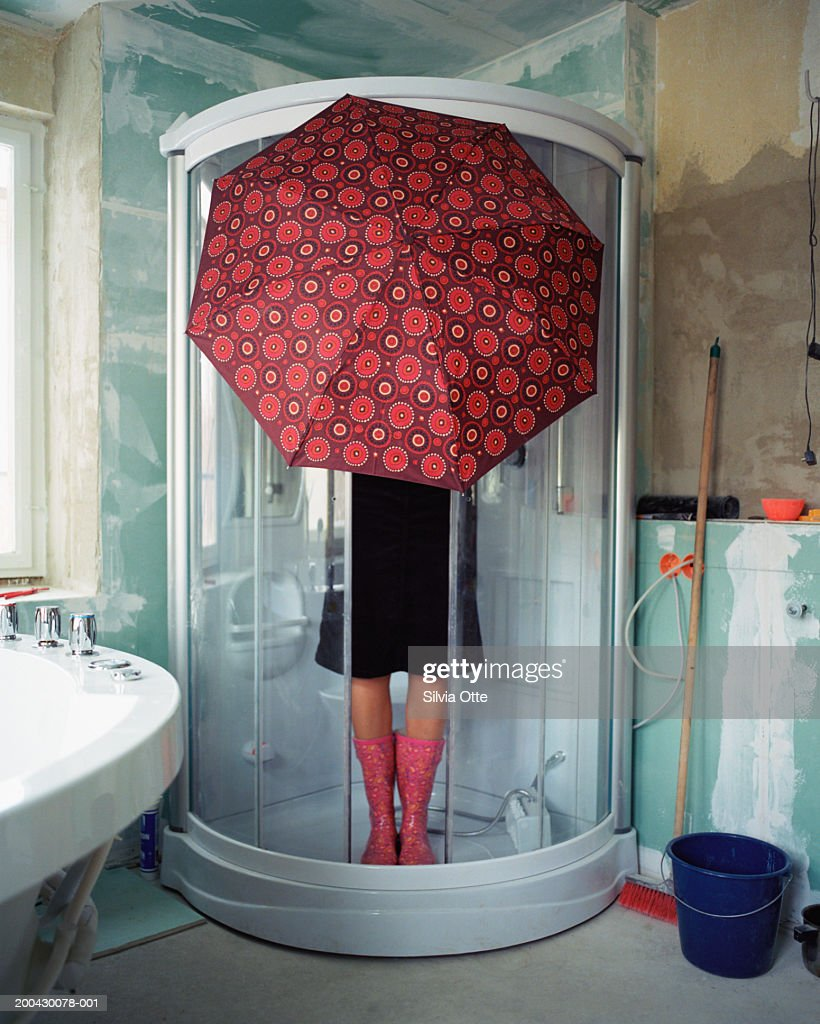 Woman standing under umbrella in shower stall : Stock Photo