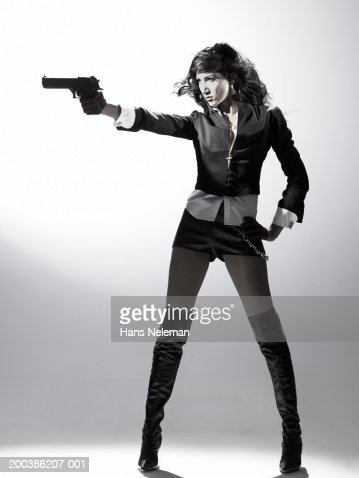 Woman standing up, pointing gun,  side view : Stock Photo