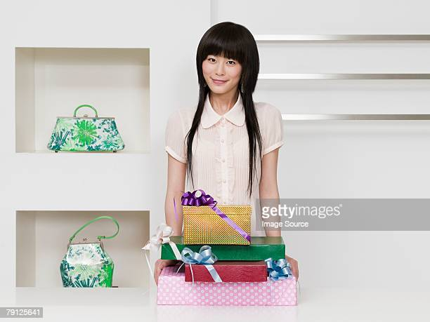 Woman standing with a stack of gifts