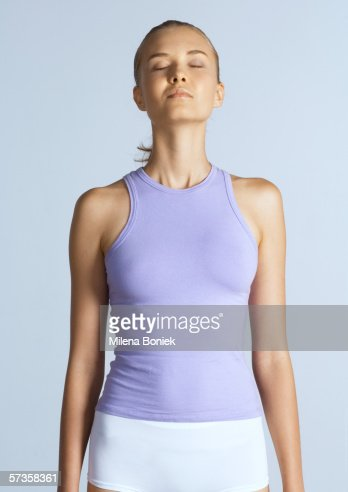 Woman standing with arms by sides and eyes closed
