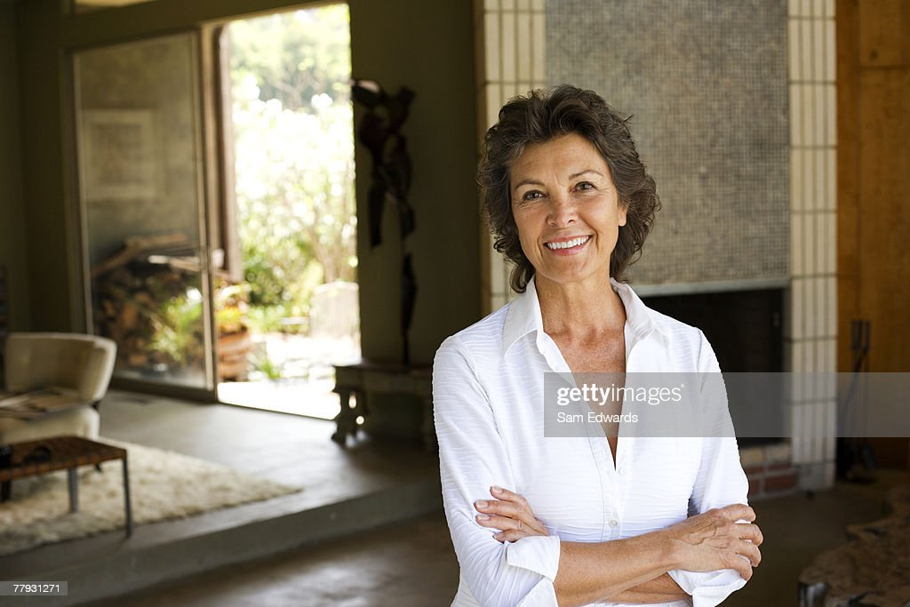 Woman standing with arms crossed smiling in modern home : Stock Photo