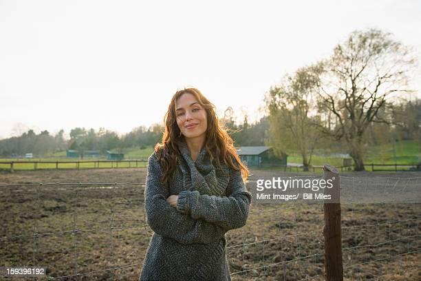 A woman standing with arms folded, by a paddock in an animal sanctuary.