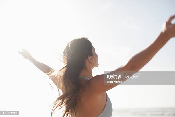 Woman standing with arms outstretched on beach