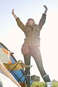 Woman standing with arms raised at campsite