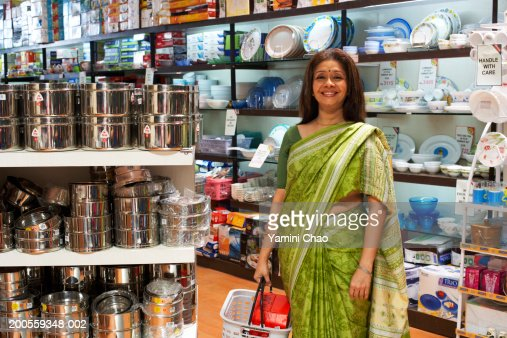 Woman standing with basket in supermarket, portrait : Stock Photo