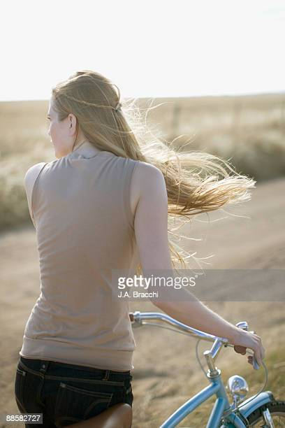 Woman standing with bicycle on country road