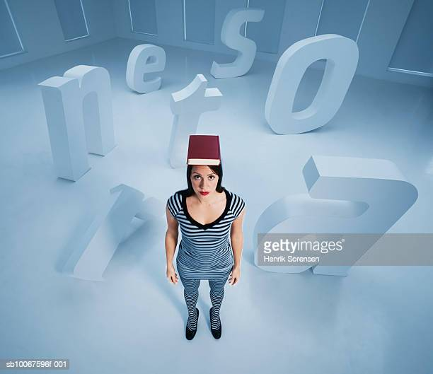 Woman standing with book on head, surrounded by big letters