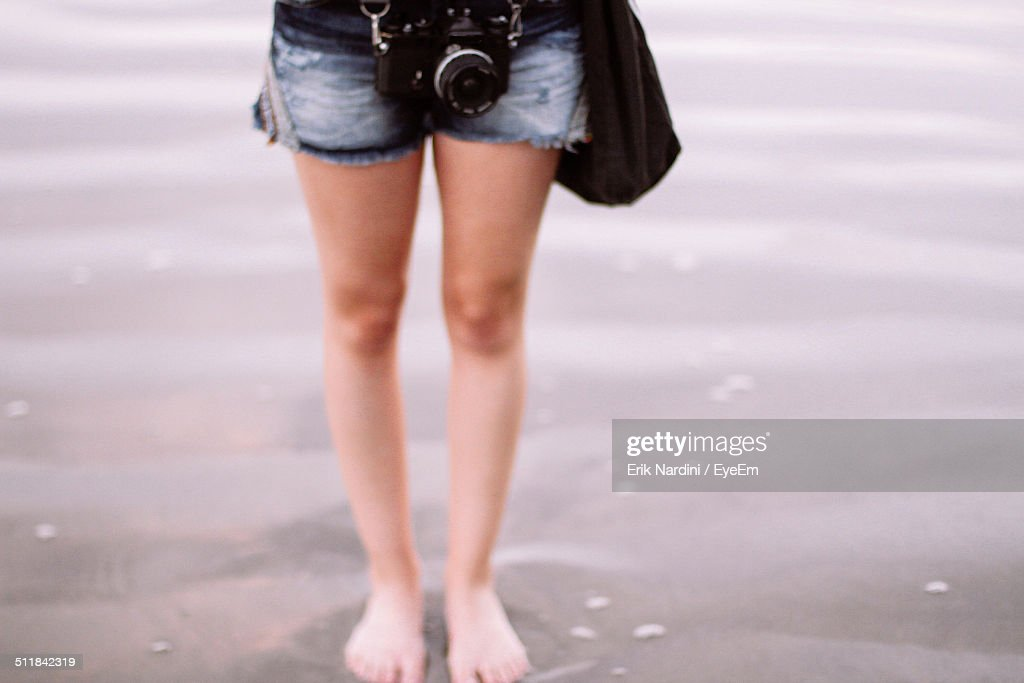 Woman standing with camera on beach