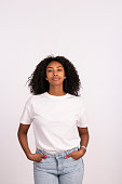 Beautiful young woman standing with hands in the pocket, looking at camera with a serious facial expression. The woman with a natural look, no makeup at all, wearing white t-shirt and jeans. Waist up