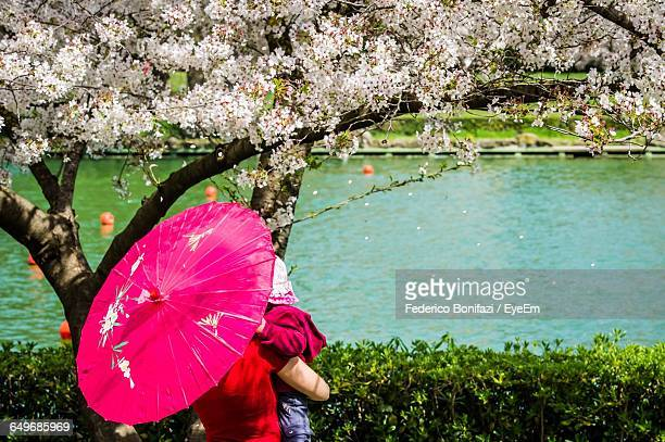 Woman Standing With Her Child Near Cherry Tree At Lakeside