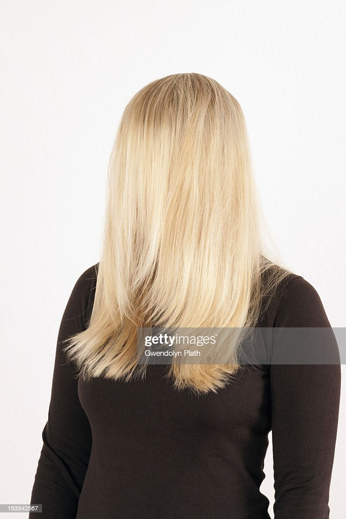 A woman standing with her long, blond hair combed forward covering her face : Stock Photo