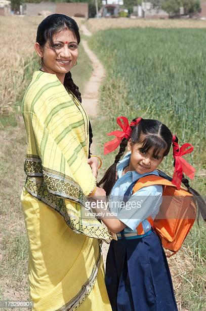 Woman standing with her schoolgirl in the field, Sohna, Haryana, India
