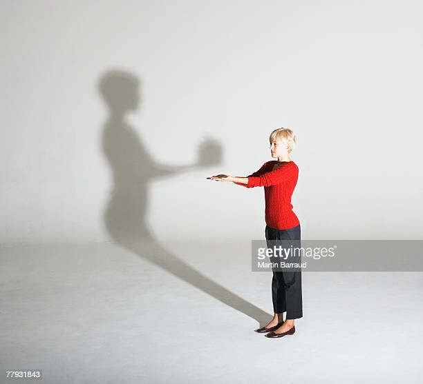 Woman standing with her shadow giving her a gift