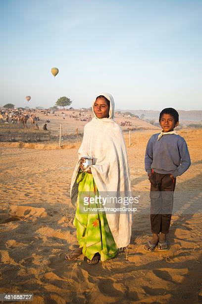 Woman standing with her son and holding a lota in desert Pushkar Ajmer Rajasthan India