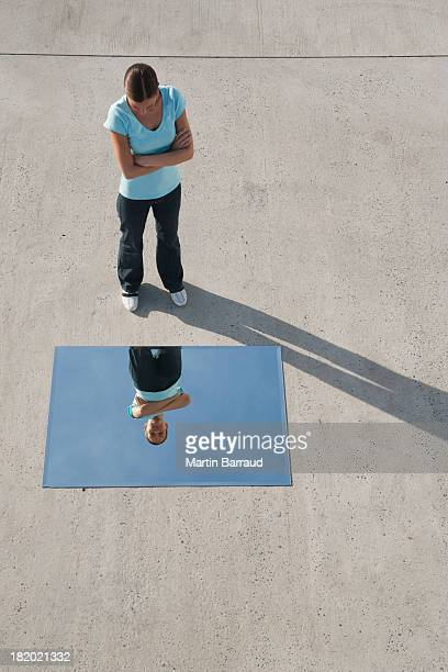 woman standing with mirror on ground and reflection