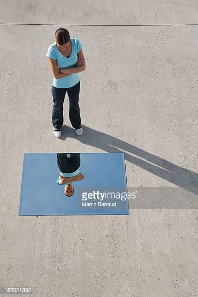 Frau stehend mit Spiegel auf Boden und Reflexion